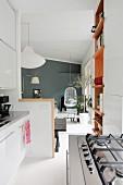 Gasherd und weisse Küchenzeile in offenem Wohnbereiche, im Hintergrund Hängestuhl vor grauer Wand