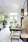 Rustikaler Holztisch mit Sitzbank und Klassikerstühlen in offenem Wohnraum mit Podest