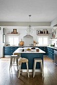 Cuntry-house kitchen with blue base units, free-standing counter and classic metal bar stools