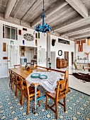 Rustic dining area with blue and white floor tiles in loft apartment