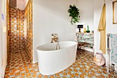 Free-standing modern bathtub in eclectic bathroom with shower area and ornate floor and wall tiles