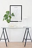 Grüne Zimmerpflanze, Kerzenhalter und Panton-Lampe auf filigranem Konsolentisch aus Böcken und Glasplatte