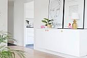 Weisser Sideboard mit Zimmerblume, Ananas-Tischlampe und angelehnten Bildern in der Diele