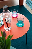 Glasses and bottle on water on round red side table