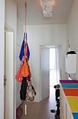 Von der Decke hängendes Seil als Garderobe mit Handtaschen