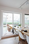 Long wooden dining table and white classic chairs next to terrace window
