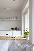 View past white sofa with scatter cushions to dining table and kitchen counter