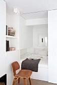 weiße Schlafnische mit Schiebetür in kleinem Apartment