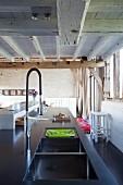 Kücheninsel mit Designer-Spülbecken und Armatur in umgebauter Scheune mit rustikaler Holzbalkendecke