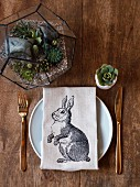 Linen napkin with rabbit motif on place setting with miniature terrarium and succulent in egg cup on wooden table