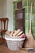 Firewood basket with hand-sewn handle on woven felt border next to tiled stove