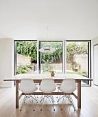 weiße Klassiker Schalenstühle an Holztisch vor Glasschiebetüren