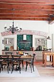 Küchenzeile im Landhausstil und Essbereich in offener Küche mit Holzbalkendecke