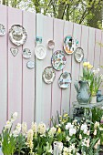 Decorative wall plates mounted on pastel board fence