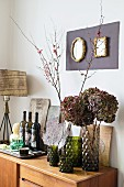 Branches of blossom and hydrangeas in glass vases next to wine bottles on sideboard