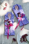 Cutlery bags made from folded napkins and decorated with astrantia