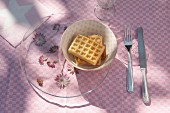 Astrantia under glass plate and waffles in bowl