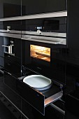 A kitchen cupboard with a shiny black surface, a built-in oven and plates in an open warming drawer