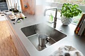 A stainless steel work surface with an integrated sink and a tap with a hot water function