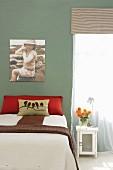 Bett mit drapierten Kissen und Tagesdecke vor grün getönter Wand