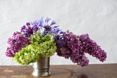 Pewter vase of lilac, hydrangeas and cornflowers
