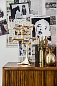 Gold candlesticks and vase in front of wall covered in black and white photos and newspaper pages