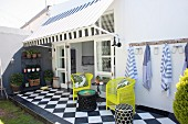 Yellow chairs and chequered floor on summer terrace