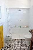 Offene Dusche, davor gemusterte Fliesen