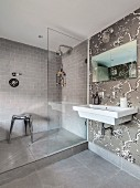 Shower area and floral wallpaper in elegant bathroom in shades of grey