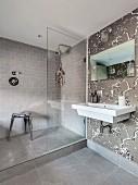 Elegantes Bad in Grautönen mit Duschbereich und floraler Tapete an Wand