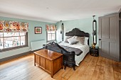 Vintage bed with wickerwork frame and wooden trunk in renovated bedroom with oak floor
