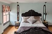 Nostalgisches Bett mit Korbgeflecht und symmetrisch angeordneten Nachttischen, Wandspiegel und Pendelleuchten