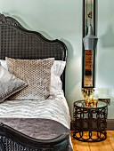 Metal bedside table with glass top next to vintage bed with wicker frame