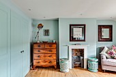 Antique chest of drawers next to traditional fireplace and armchair in bedroom