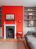 Vintage fireplace in red chimney breast flanked by grey fitted shelving