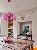 Rustic iron table with wooden top below pink pendant lamp and artwork on top of sideboard in niche