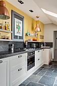 weiße Küchenzeile mit Granit-Arbeitsplatte und Wandboards an gelber Wand