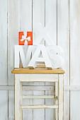 Buchstaben auf einem Hocker vor weißer Bretterwand