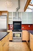 Cooker, dark worksurfaces and cabinets in modern kitchen