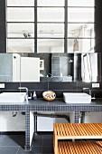 Twin countertop sinks in minimalist bathroom of loft apartment with industrial interior window