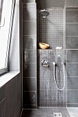 Grey-tiled shower area with mosaic tiles and wall-mounted fittings