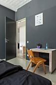 Minimalist desk against dark grey wall in bedroom