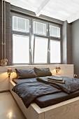 Custom double bed below window in minimalist bedroom