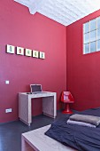 Laptop desk against red wall in minimalist workspace in corner of bedroom with industrial windows