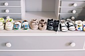 Row of babies booties on grey chest of drawers