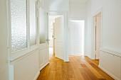 Leere Altbauwohnung mit Blick vom Flur auf offene Türen