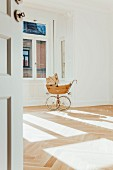Pram in empty room with open door