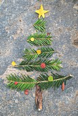 Sprigs of fir and pieces of leaf and bark arranged in shape of a Christmas tree