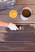 Hand applying varnish to decking with paintbrush