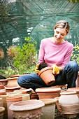 Frau zwischen Terracotta-Töpfen beim Umtopfen einer Pflanze